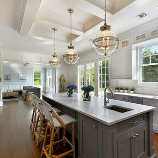 Design ideas for a mid-sized traditional kitchen in New York with recessed-panel cabinets, white cabinets, grey splashback, porcelain splashback, medium hardwood floors, with island, an undermount sink and panelled appliances.