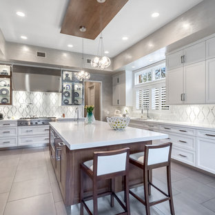 Photo of a mid-sized transitional u-shaped eat-in kitchen in New York with recessed-panel cabinets, white cabinets, white splashback, stainless steel appliances, with island, an undermount sink, solid surface benchtops, porcelain floors and mosaic tile splashback.