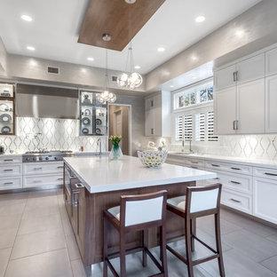 Klassisk inredning av ett mellanstort kök, med luckor med infälld panel, vita skåp, vitt stänkskydd, rostfria vitvaror, en köksö, en undermonterad diskho, bänkskiva i koppar, klinkergolv i porslin och stänkskydd i mosaik