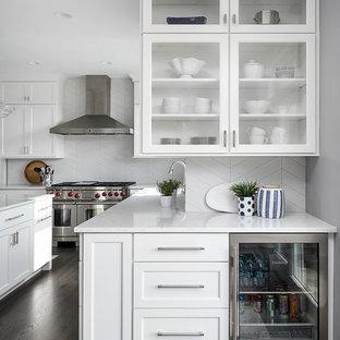 Große Klassische Küche mit weißen Schränken, Küchenrückwand in Weiß, Rückwand aus Porzellanfliesen, Küchengeräten aus Edelstahl, Kücheninsel, weißer Arbeitsplatte, Glasfronten, dunklem Holzboden, Quarzit-Arbeitsplatte und braunem Boden in Chicago