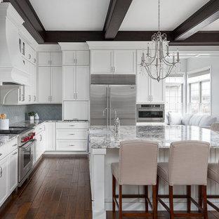 Inspiration för stora klassiska flerfärgat kök, med en rustik diskho, vita skåp, granitbänkskiva, stänkskydd i porslinskakel, rostfria vitvaror, mörkt trägolv, en köksö och brunt golv