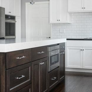 Klassische Wohnküche in L-Form mit Schrankfronten mit vertiefter Füllung, braunen Schränken, Granit-Arbeitsplatte, Küchenrückwand in Weiß, Rückwand aus Keramikfliesen, Küchengeräten aus Edelstahl, braunem Holzboden, Kücheninsel, braunem Boden und weißer Arbeitsplatte in Chicago