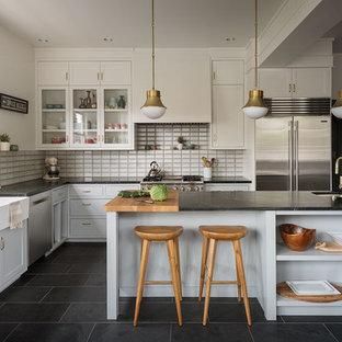 Inredning av ett klassiskt svart svart l-kök, med en rustik diskho, luckor med glaspanel, beige skåp, beige stänkskydd, rostfria vitvaror, en köksö och svart golv