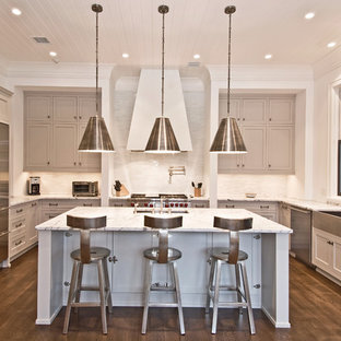 Transitional u-shaped kitchen photo in New York with a farmhouse sink, stainless steel appliances, gray cabinets, recessed-panel cabinets, marble countertops and white backsplash
