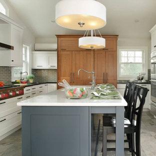 Idéer för ett stort klassiskt u-kök, med en undermonterad diskho, skåp i shakerstil, vita skåp, grått stänkskydd, stänkskydd i tunnelbanekakel, rostfria vitvaror, kalkstensgolv och en köksö