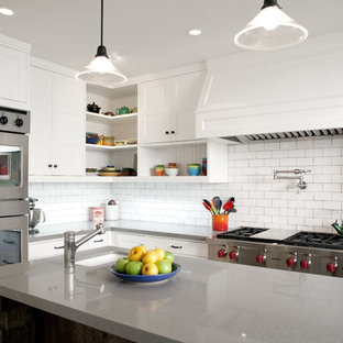 Mid-sized transitional kitchen pictures - Inspiration for a mid-sized transitional u-shaped kitchen remodel in Los Angeles with quartz countertops, stainless steel appliances, an island, white backsplash and subway tile backsplash