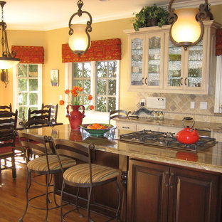 Photo of a traditional eat-in kitchen in Los Angeles with glass-front cabinets, beige cabinets and beige splashback.
