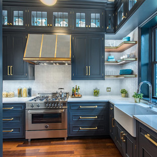 Transitional enclosed kitchen designs - Inspiration for a transitional l-shaped medium tone wood floor and brown floor enclosed kitchen remodel in New York with a farmhouse sink, shaker cabinets, blue cabinets, gray backsplash, stainless steel appliances and no island