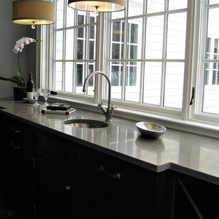 Inspiration for a large traditional u-shaped separate kitchen in New York with a farmhouse sink, shaker cabinets, white cabinets, concrete benchtops, beige splashback, matchstick tile splashback, stainless steel appliances, dark hardwood floors, with island, brown floor and grey benchtop.