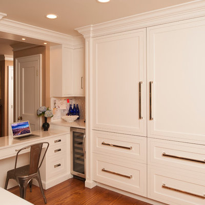 Example of a transitional l-shaped open concept kitchen design in New York with shaker cabinets, beige cabinets, solid surface countertops and stainless steel appliances