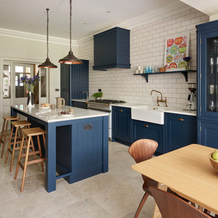 Photo of a classic single-wall kitchen/diner in Sussex with a belfast sink, shaker cabinets, blue cabinets, white splashback, metro tiled splashback, an island and beige floors.