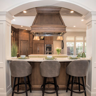 Inspiration for a large transitional l-shaped eat-in kitchen in San Francisco with an undermount sink, recessed-panel cabinets, quartzite benchtops, glass tile splashback, panelled appliances, multiple islands, dark wood cabinets, medium hardwood floors, beige floor and beige benchtop.