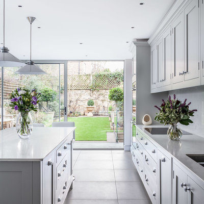 Example of a transitional kitchen design in London with shaker cabinets, gray cabinets, quartzite countertops, a double-bowl sink and an island