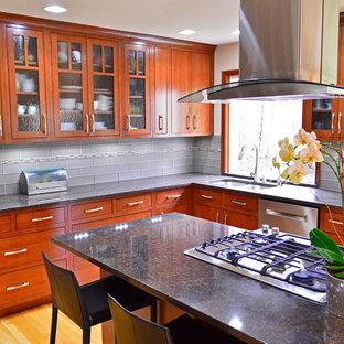 Foto på ett stort vintage kök, med en undermonterad diskho, släta luckor, skåp i mörkt trä, bänkskiva i kvarts, grått stänkskydd, stänkskydd i tunnelbanekakel, rostfria vitvaror, mellanmörkt trägolv, en köksö och brunt golv