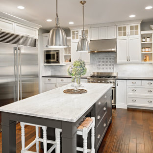 Inspiration for a mid-sized transitional u-shaped dark wood floor kitchen remodel in San Francisco with a farmhouse sink, shaker cabinets, white cabinets, marble countertops, white backsplash, stainless steel appliances, an island and stone tile backsplash