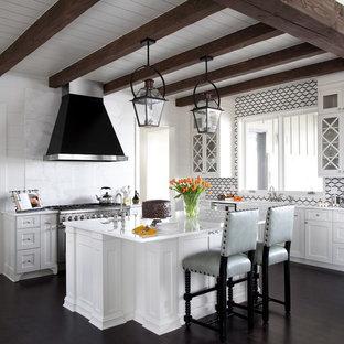 ニューオリンズの広いトランジショナルスタイルのおしゃれなキッチン (エプロンフロントシンク、ガラス扉のキャビネット、白いキャビネット、濃色無垢フローリング、大理石カウンター、白いキッチンパネル、石スラブのキッチンパネル、シルバーの調理設備、白いキッチンカウンター、表し梁) の写真