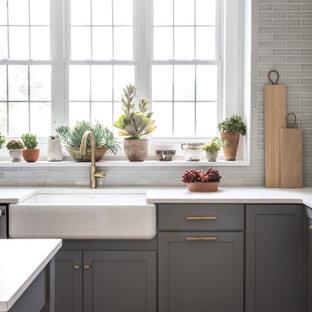 Große Klassische Küche in L-Form mit Küchenrückwand in Grau, Rückwand aus Keramikfliesen, braunem Holzboden, Kücheninsel, braunem Boden, weißer Arbeitsplatte, Landhausspüle, Schrankfronten im Shaker-Stil und grauen Schränken in Boston