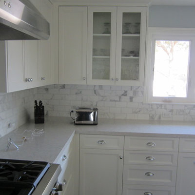 Eat-in kitchen - mid-sized transitional u-shaped eat-in kitchen idea in Los Angeles with a farmhouse sink, shaker cabinets, white cabinets, quartzite countertops, white backsplash, stone tile backsplash and stainless steel appliances