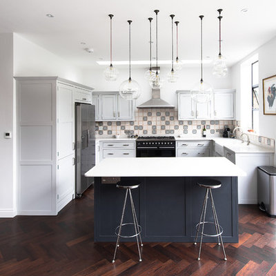 Example of a mid-sized transitional dark wood floor open concept kitchen design in London with a farmhouse sink, shaker cabinets, gray cabinets, quartzite countertops, ceramic backsplash, stainless steel appliances and an island
