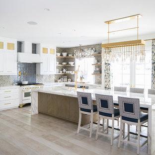 Идея дизайна: угловая кухня в стиле современная классика с обеденным столом, раковиной в стиле кантри, фасадами с утопленной филенкой, белыми фасадами, серым фартуком, белой техникой, светлым паркетным полом, островом и бежевым полом