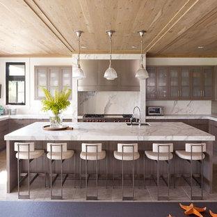 ニューヨークの広いトランジショナルスタイルのおしゃれなキッチン (シングルシンク、フラットパネル扉のキャビネット、グレーのキャビネット、白いキッチンパネル、パネルと同色の調理設備、大理石カウンター、石スラブのキッチンパネル、セラミックタイルの床、ベージュの床) の写真
