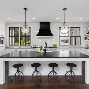 Traditional u-shaped kitchen in San Francisco with a submerged sink, shaker cabinets, white cabinets, white splashback, stainless steel appliances, dark hardwood flooring, an island, brown floors and black worktops.