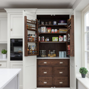 Inspiration for a large classic l-shaped kitchen pantry in Other with shaker cabinets, white cabinets, black appliances, an island, beige floors and white worktops.
