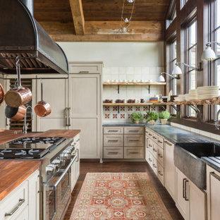 Rustik inredning av ett stort grå grått kök, med en rustik diskho, skåp i shakerstil, beige skåp, bänkskiva i täljsten, vitt stänkskydd, stänkskydd i porslinskakel, rostfria vitvaror, mellanmörkt trägolv, en köksö och brunt golv