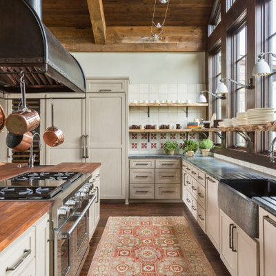 Eat-in kitchen - large rustic u-shaped medium tone wood floor, brown floor and wood ceiling eat-in kitchen idea in Houston with a farmhouse sink, shaker cabinets, beige cabinets, soapstone countertops, white backsplash, porcelain backsplash, stainless steel appliances, an island and gray countertops
