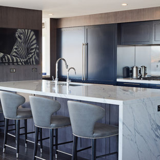 Inspiration for a large transitional galley open plan kitchen in Sydney with an undermount sink, shaker cabinets, mirror splashback, with island, grey benchtop, blue cabinets, marble benchtops, stainless steel appliances, dark hardwood floors and black floor.