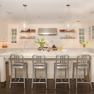 Transitional kitchen designs - Example of a transitional u-shaped dark wood floor kitchen design in Other with an undermount sink, shaker cabinets, white cabinets, white backsplash, stainless steel appliances and an island