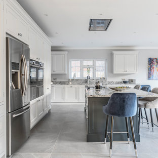 Large classic l-shaped kitchen/diner in Berkshire with shaker cabinets, grey cabinets, marble worktops, grey splashback, marble splashback, integrated appliances, an island, grey worktops and grey floors.
