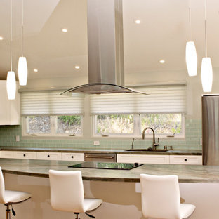 This is an example of a mid-sized transitional l-shaped eat-in kitchen in San Diego with a drop-in sink, shaker cabinets, white cabinets, quartz benchtops, green splashback, glass tile splashback, stainless steel appliances, light hardwood floors, with island, brown floor and green benchtop.