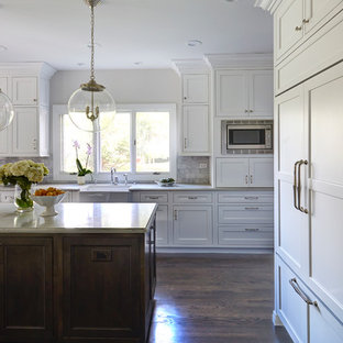 Transitional kitchen designs - Transitional dark wood floor kitchen photo in Chicago with a farmhouse sink, beaded inset cabinets, white cabinets, quartz countertops, white backsplash, stone tile backsplash, paneled appliances and an island