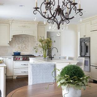 Idéer för ett stort klassiskt beige kök, med en undermonterad diskho, luckor med upphöjd panel, beige skåp, bänkskiva i kvarts, beige stänkskydd, stänkskydd i marmor, integrerade vitvaror, mörkt trägolv, en köksö och brunt golv
