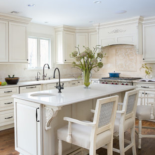 ニューアークの広いトラディショナルスタイルのおしゃれなキッチン (アンダーカウンターシンク、ベージュキッチンパネル、無垢フローリング、茶色い床、落し込みパネル扉のキャビネット、ベージュのキャビネット、クオーツストーンカウンター、大理石のキッチンパネル、パネルと同色の調理設備、ベージュのキッチンカウンター) の写真