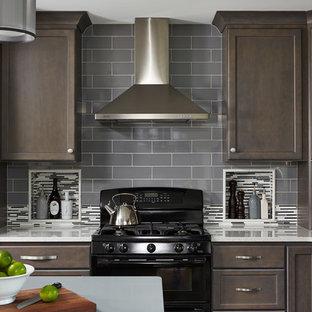 Transitional kitchen photos - Kitchen - transitional kitchen idea in Minneapolis with recessed-panel cabinets, dark wood cabinets, gray backsplash, subway tile backsplash, black appliances and an island