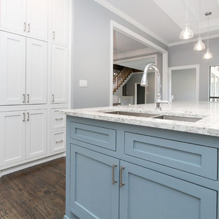 Inspiration for a large transitional u-shaped open plan kitchen in Dallas with a double-bowl sink, shaker cabinets, white cabinets, quartzite benchtops, white splashback, stone slab splashback, stainless steel appliances, dark hardwood floors, with island, brown floor and turquoise benchtop.