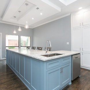 Photo of a large transitional u-shaped open plan kitchen in Dallas with a double-bowl sink, shaker cabinets, white cabinets, quartzite benchtops, white splashback, stone slab splashback, stainless steel appliances, dark hardwood floors, with island, brown floor and turquoise benchtop.