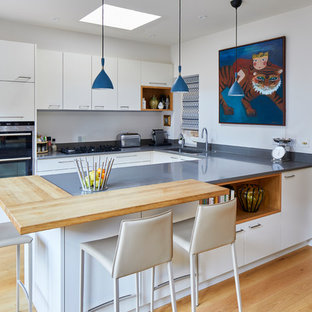 Classic u-shaped kitchen in London with a submerged sink, flat-panel cabinets, white cabinets, stainless steel appliances, medium hardwood flooring, brown floors and grey worktops.