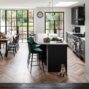 Photo of a traditional galley kitchen/diner in London with shaker cabinets, black cabinets, white splashback, metro tiled splashback, black appliances, medium hardwood flooring, an island, brown floors and white worktops.