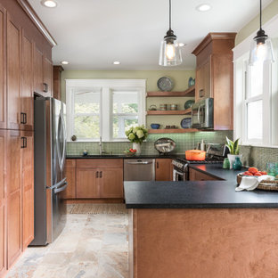 Design ideas for a mid-sized transitional l-shaped eat-in kitchen in DC Metro with an undermount sink, shaker cabinets, granite benchtops, green splashback, glass tile splashback, stainless steel appliances, porcelain floors, no island, multi-coloured floor, black benchtop and medium wood cabinets.