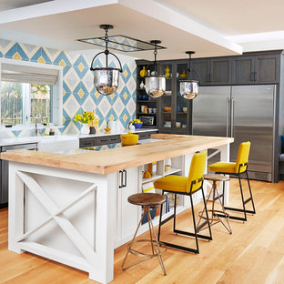 Large transitional u-shaped medium tone wood floor open concept kitchen photo in Other with a farmhouse sink, shaker cabinets, gray cabinets, wood countertops, blue backsplash, ceramic backsplash, stainless steel appliances and an island