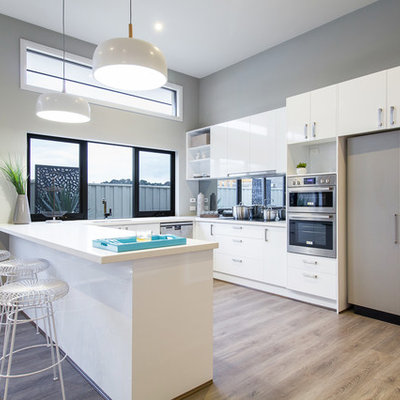 Kitchen - transitional u-shaped light wood floor kitchen idea in Other with flat-panel cabinets, white cabinets, paneled appliances and a peninsula