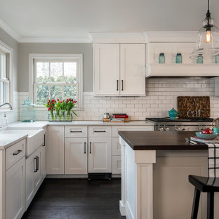 Large traditional eat-in kitchen ideas - Inspiration for a large timeless l-shaped dark wood floor and brown floor eat-in kitchen remodel in Detroit with shaker cabinets, white cabinets, white backsplash, subway tile backsplash, stainless steel appliances, an island, a farmhouse sink, quartz countertops and white countertops