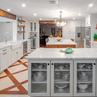 Example of a mid-sized transitional travertine floor and beige floor eat-in kitchen design in Phoenix with a farmhouse sink, shaker cabinets, white cabinets, gray backsplash, subway tile backsplash, stainless steel appliances, an island and white countertops