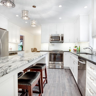 Large transitional kitchen ideas - Example of a large transitional u-shaped kitchen design in DC Metro with an undermount sink, recessed-panel cabinets, white cabinets, granite countertops, white backsplash, subway tile backsplash, stainless steel appliances and an island