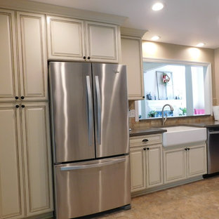 Design ideas for a mid-sized transitional galley separate kitchen in Other with a farmhouse sink, raised-panel cabinets, beige cabinets, solid surface benchtops, multi-coloured splashback, stone tile splashback, stainless steel appliances, vinyl floors and no island.