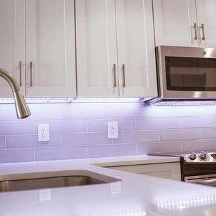 Klassisk inredning av ett mellanstort l-kök, med en undermonterad diskho, skåp i shakerstil, vita skåp, bänkskiva i kvarts, stänkskydd i tunnelbanekakel, rostfria vitvaror, en halv köksö och beiget golv