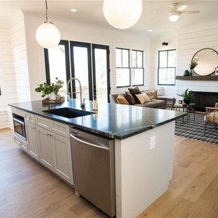 マイアミの中サイズのトランジショナルスタイルのおしゃれなキッチン (アンダーカウンターシンク、シェーカースタイル扉のキャビネット、白いキャビネット、オニキスカウンター、白いキッチンパネル、木材のキッチンパネル、シルバーの調理設備の、淡色無垢フローリング、ベージュの床、黒いキッチンカウンター) の写真